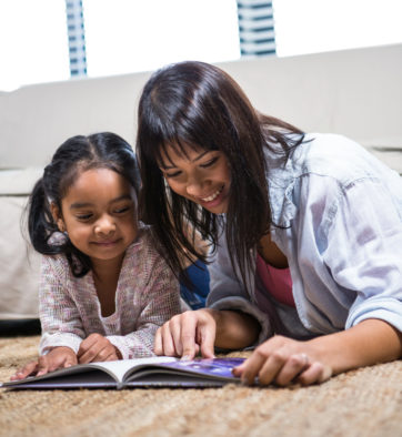 Happy young mother reading a book with her daughter