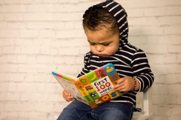 boy-in-black-and-white-striped-long-sleeve-shirt-reading-book-1
